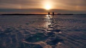 两个男性日落远足者走的阳光的人剪影在未触动过的雪风景的 冒险旅途旅行 股票录像