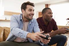 两个男性朋友坐沙发在打电子游戏的休息室 库存图片