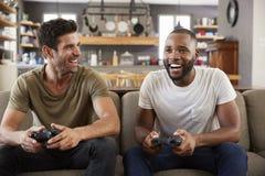 两个男性朋友坐沙发在打电子游戏的休息室 免版税库存照片