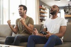 两个男性朋友坐沙发在打电子游戏的休息室 图库摄影