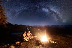 两个男性远足者有休息在充分野营在晚上在美丽的夜空下星和银河 长期风险 图库摄影