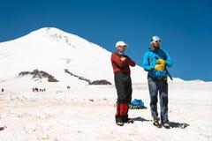 两个登山人在正确的滑动的训练谈话在与冰斧的倾斜不停刹车的反对背景 免版税库存照片