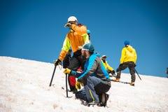 两个登山人在正确的滑动的训练谈话在与冰斧的倾斜不停刹车的 免版税图库摄影