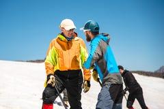 两个登山人在正确的滑动的训练谈话在与冰斧的倾斜不停刹车的 免版税库存照片