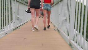 两个白女孩的桃红色腿特写镜头视图沿狭窄的吊桥走 股票视频