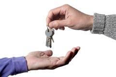 两个白种人人接受某一钥匙的` s手,一个给和一个隔绝在与裁减路线的白色背景 免版税库存图片