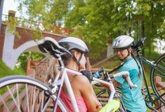 两个白种人女运动员解决与自行车 库存照片