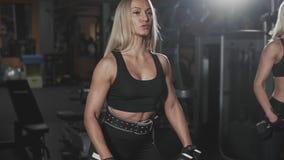 两个白肤金发的女孩锻炼黑暗的健身房的 刺激健康生活方式 影视素材