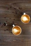 两个白色杯子在一张木桌上的热奶咖啡 免版税库存照片