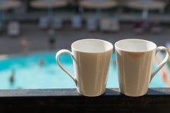 两个白色杯子在阳台在旅馆的背景中站立,大厦和水池是可看见的 在那里一个杯子上 库存图片