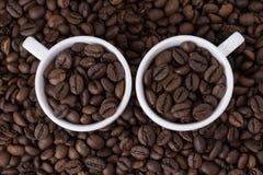 两个白色杯子有咖啡豆背景 库存图片