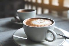 两个白色杯子的特写镜头图象在桌上的热的咖啡 免版税库存照片