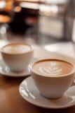 两个白色杯子芬芳热奶咖啡在一张木桌上站立 咖啡用在桌上的牛奶,正面图 库存照片