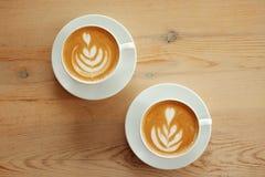 两个白色杯子芬芳热奶咖啡在一张木桌上站立 咖啡用在桌上的牛奶,顶视图 免版税库存图片