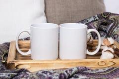 两个白色杯子,对在一个木盘子,大模型的杯子 舒适家,木背景、棉花和羊毛装饰,冬天礼物 免版税库存图片