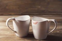两个白色杯子,他们中的一个佩带唇膏、人关系和妇女,背景的老木 免版税库存图片