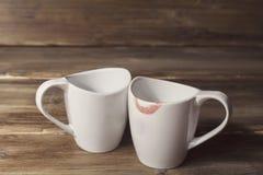 两个白色杯子,他们中的一个佩带唇膏、人关系和妇女,背景的老木 免版税图库摄影