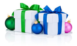 两个白色礼物盒栓了在白色和最高荣誉弓和圣诞节球隔绝的绿色 图库摄影