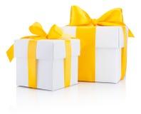 两个白色礼物盒栓了被隔绝的一把黄色缎丝带弓 免版税库存图片