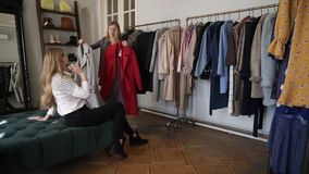 两个的女孩或一起购物双的姐妹:长发年轻白肤金发的女性尝试新的灰色和红色外套一会儿 影视素材