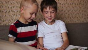 读两个的男孩坐长沙发和书 股票录像