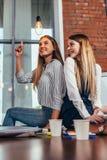 两个相当女学生一起坐书桌在教室,指向电灯泡的女孩喜欢有精采 免版税库存照片