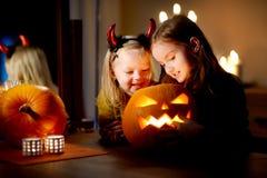 两个相当年轻姐妹在万圣夜打扮一起雕刻南瓜 库存照片