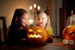 两个相当年轻姐妹在万圣夜打扮一起雕刻南瓜 库存图片