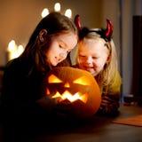 两个相当年轻姐妹在万圣夜打扮一起雕刻南瓜 免版税库存照片