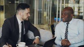 两个确信的企业同事谈论关于合作在会议期间在现代咖啡馆 股票视频