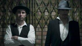 两个确信的穿着体面的人画象站立在彼此附近的帽子的,等待 两人同时离开 股票录像
