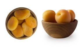 两个碗用杏干和强奸杏子在白色隔绝的一个木碗 干果子和新鲜水果与拷贝空间 库存图片