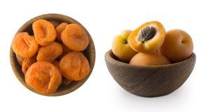 两个碗用杏干和强奸杏子在白色隔绝的一个木碗 干果子和新鲜水果与拷贝空间 免版税库存图片