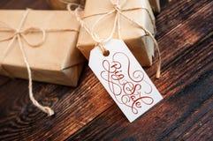 两个礼物盒和标记与大销售在牛皮纸和木背景发短信 手书面书法和字法 库存照片