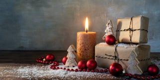两个礼物盒和灼烧的蜡烛、红色圣诞节中看不中用的物品和s 免版税库存图片