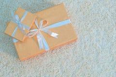 两个礼物盒金子颜色栓与丝带在一张白色软的地毯说谎 为假日新年做准备,圣诞节,生日 库存照片