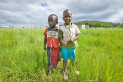 两个祖鲁族人黑人男孩在Zululand乡区与村庄的在背景,南非中 库存图片
