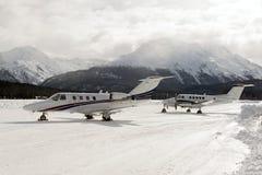 两个私人喷气式飞机在圣盛生积雪的机场在阿尔卑斯瑞士在冬天 免版税库存图片