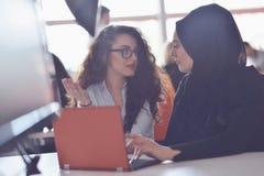 两个穆斯林研究他们的膝上型计算机的女商人 库存照片