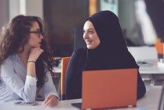 两个穆斯林研究他们的膝上型计算机的女商人 免版税库存照片