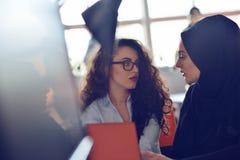 两个穆斯林研究他们的膝上型计算机的女商人 免版税库存图片