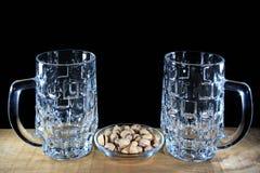两个空的啤酒杯和开心果反对黑背景 库存图片