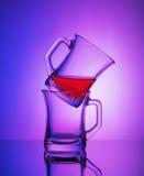 两个空的水晶杯子接近的看法以其余在梯度蓝色和紫色背景的茶 图库摄影