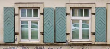 两个窗口在有开放木快门的老房子里 库存照片