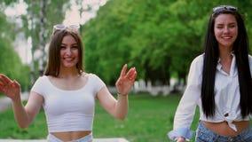 两个笑的美丽的女孩在公园乘坐在GyroScooter在一个晴朗的夏日 股票视频
