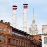 两个管子的不同的时期混合和大厦反对天空的 工厂老工厂厂房从红砖的 免版税库存照片