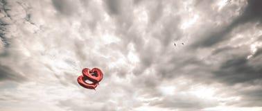 两个红色心形的气球在天空中 与风雨如磐的天空的美好的背景 库存图片