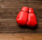 两个红色拳击手套在木棕色背景,空的空间垂悬了 免版税库存照片