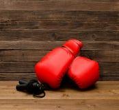 两个红色拳击手套在木棕色背景,跨越横线空的空间说谎 免版税库存照片