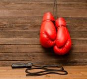 两个红色拳击手套在木棕色背景,跳绳垂悬了 图库摄影